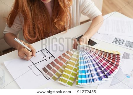 Closeup portrait of young woman working with floor plans and color swatches choosing interior design for new house
