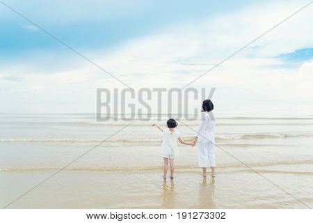 Happy Asian family mother and daughter standing on beach looking and point something in sea. Happy family summer vacation concept.