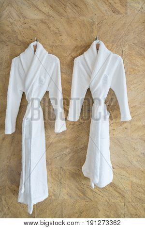 The image of couple white bathrobes on a hanger in bathroom.