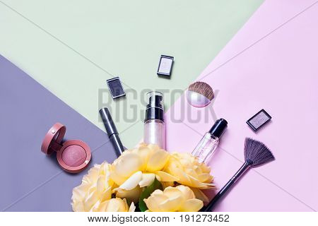 Creative flat lay of fashion bright nail polishes and decorative cosmetic on a colorful background with yellow roses. Minimal style. Copy space. Beauty blogger concept. Top view.