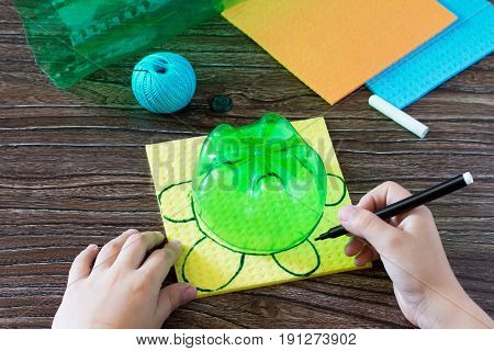 A Child Draws Details Of A Children's Hand-craft For Money Piggy Bank. Handmade. Project Of Children