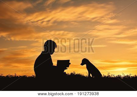Silhouette boy reading a book with little dog on the sky sunset color of vintage tone