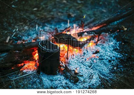 Food Is Cooked Over A Fire In An Old Vintage Retro Marching Pot Dixie. German Wehrmacht Infantry Soldier's Military Equipment Of World War II.
