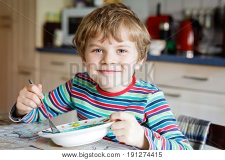 Adorable little school boy eating vegetable soup indoor. Blond child in domestic kitchen or in school canteen. Cute kid and healthy food, organic vegan soup with potato, tomato and vegetables