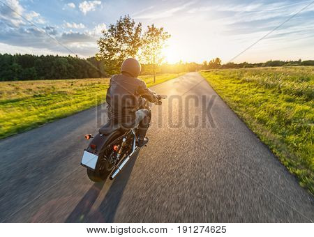 Dark motor biker riding high power motorbike in nature with beautiful sunset light. Travel and transportation. Freedom of motorbike riding