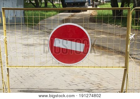 No ehtry road sign on a yellow metal fence
