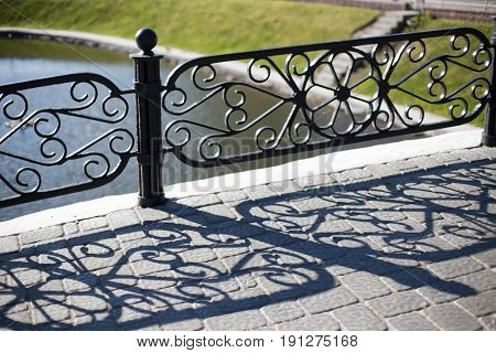 Forged Fence. A Long Shadow On The Sidewalk.