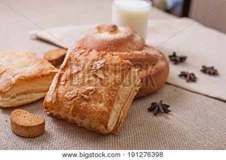 Fresh pastries and a glass of milk. Canvas tablecloth. Side view.