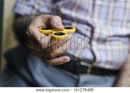closeup of an old caucasian man playing with a yellow fidget spinner