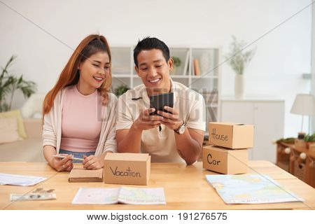 Portrait of young Asian couple planning family budget saving  for house, car and vacation