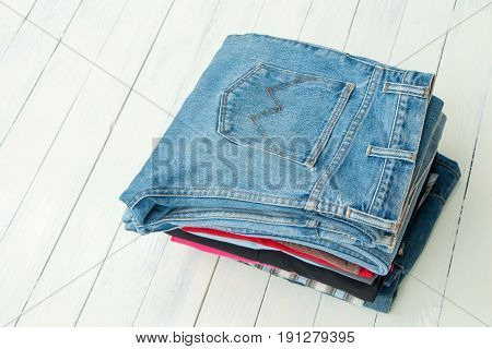 Close up denim jeans put on white wooden table
