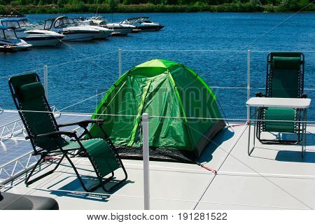 Vacation and slow lifestyle. float house good for vacation. tourist tent and chairs on of indoor beach terrace over water surface. Raft for rest on the water