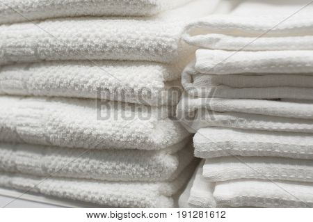 White towels stacked on a shelf in the closet.