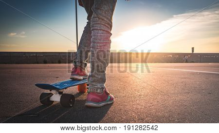 Closeup Of The Feet On The Skateboard On The Pavement