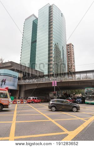KOWLOON HONG KONG - APRIL 21 2017: Skyscraper and Intersection Traffic at Morning in Kowloon Hong Kong.