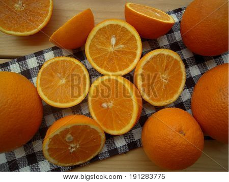 Oranges cut into halves and whole on a kitchen napkin.