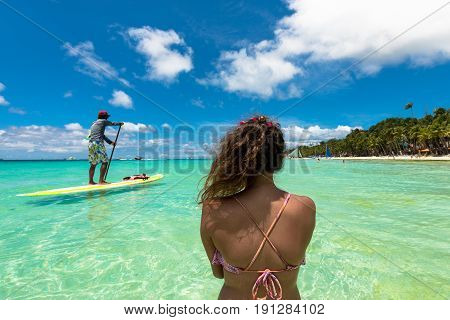 BORACAY, WESTERN VISAYAS, PHILIPPINES - MARCH 27, 2017: Woman watching a native man practicing stand up paddle at White Beach Boracay.