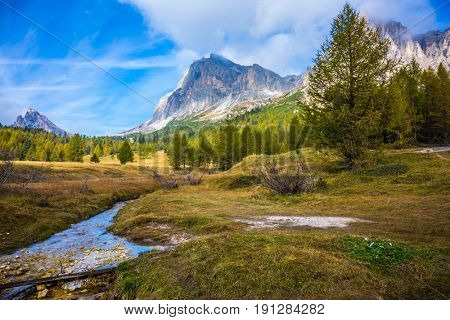 The dizzying Dolomites. Sharp rocks surround the grassy valleys. A cold fast spring flows through the valley. The concept of ecological and extreme tourism