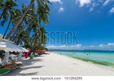 BORACAY, WESTERN VISAYAS, PHILIPPINES - MARCH 27, 2017: Coconnut trees and tents makes the White Beach a good place to relax in a sunny day at White Beach.