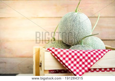 Melon fruit from organic farms in wooden box with copy space