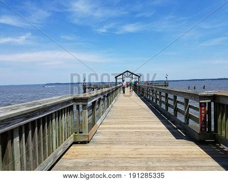 people fishing on long wooden boardwalk on river