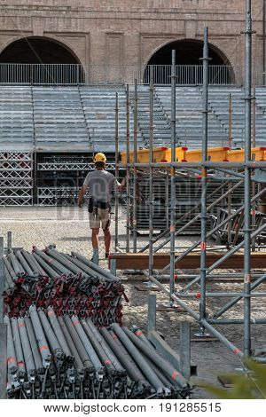 Workman with Yellow Helmet Scaffolding Elements Construction and Stacked Poles for Stage Structure Support