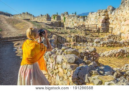 Traveler woman photographer takes shot of Archaeological Site of Ancient Mycenae, Peloponnese, Greece. Caucasian beauty blonde female photographing a ruins of defence stone walls. Europe Heritage Site