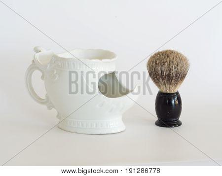 Vintage badger hair shaving brush with antique soap dish and brush holder. Isolated. White background.