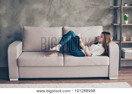 Domestic Life. Relaxed Young Lady Is Studying, Lying On The Cozy Beige Couch In Living Room At Home,