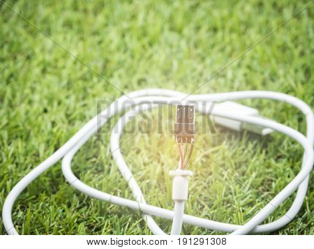 white USB cable damaged left on green grass