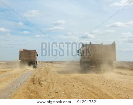 loaded truck is driving along a dirt road.