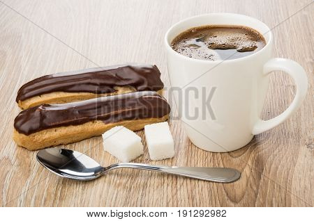 Eclairs With Chocolate, Black Coffee In Cup, Lumpy Sugar