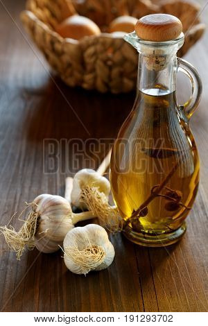 Head Of Garlic And Olive Oil Bottle On A Rustic Table
