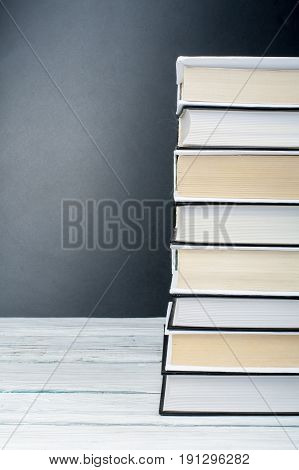 Open book, hardback black, White books on wooden table. Back to school. Copy space for text. Education business concept