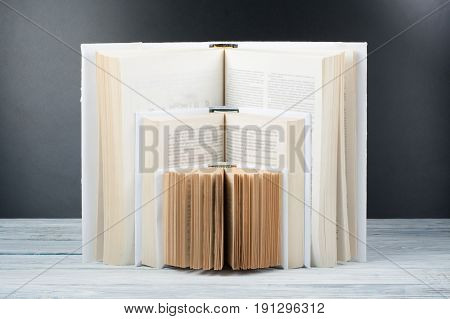 Open book. White books on wooden table, black board background. Back to school. Education business concept