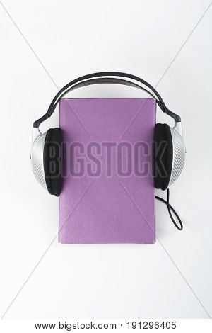 Audiobook on white background. Headphones put book, empty cover, copy space for ad text. Distance education, e-learning concept