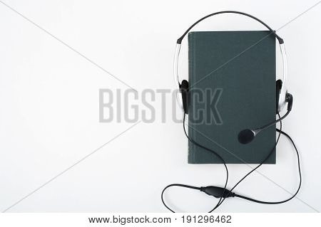 Audiobook on white background. Headphones put over green hardback book, empty cover, copy space for ad text. Distance education, e-learning concept