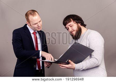 Two chefs Having Informal Meeting, one guy holds a folder.