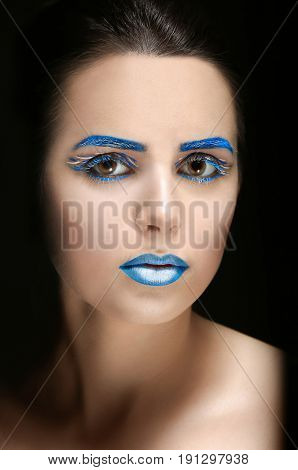 Beautiful young woman with creative makeup on black background