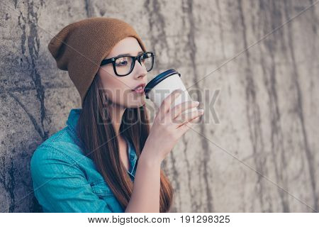 Charming Dreamy Young Girl Drinking Tea Near Concrete Wall Outdoors. She Is Sleepy And Relaxed, In C