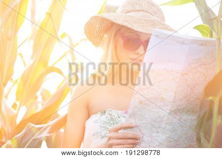 Woman reading map while standing amidst plants outdoors