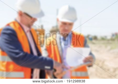 Business Blurred Background Concept: Engineers working on an industrial site