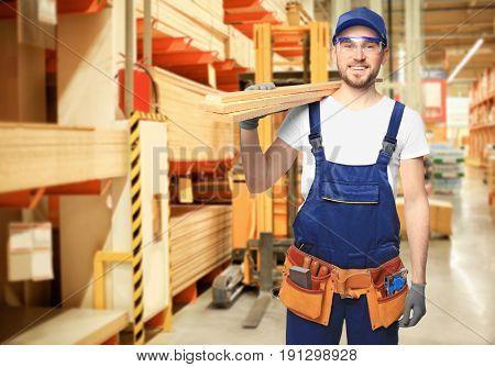 Carpenter holding wooden planks at storehouse