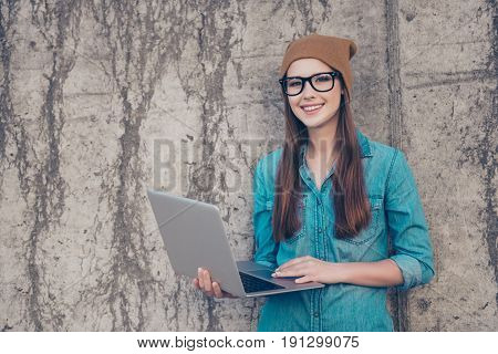 Young Stylish Student Is Working On Her Laptop Outdoors, Wearing Casual Clothes And Glasses, Hat, Ne