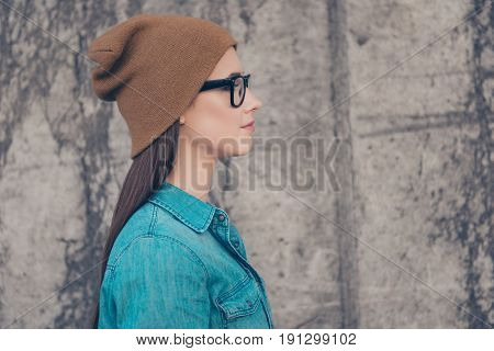 Close Up Profile Side Portrait Of Young Stylish Lady In Casual Outfit, Hat And Glasses Near Concrete