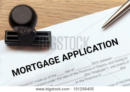 Mortgage application with rubber stamp on wooden desk