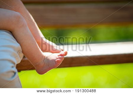 barefooted kid with covered gooseflesh sits on his mother's lap on a wooden bench in the rays of the spring sun