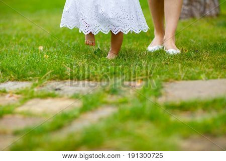 Mom leads a barefoot little daughter in a white dress on the green grass. The girl reluctantly picks her feet stepping on the barbed grass
