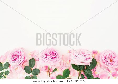 Frame of gentle pink roses, petals and leaves on white background. Flat lay, top view.