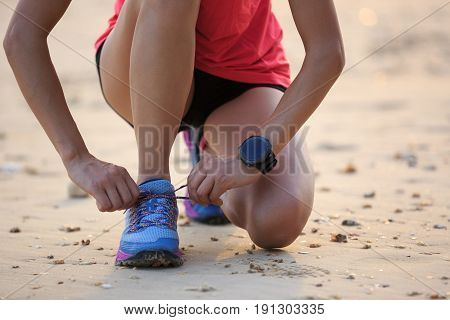 young fitness woman runner tying shoelace at sunny beach
